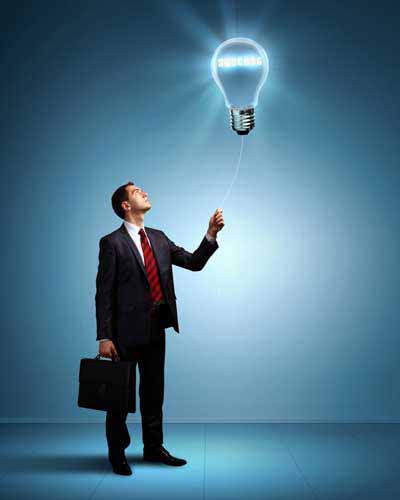 Businessman switching off bulb to reduce energy cost
